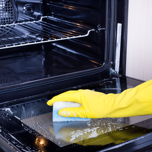 Gloved hand cleaning inside of oven with sponge
