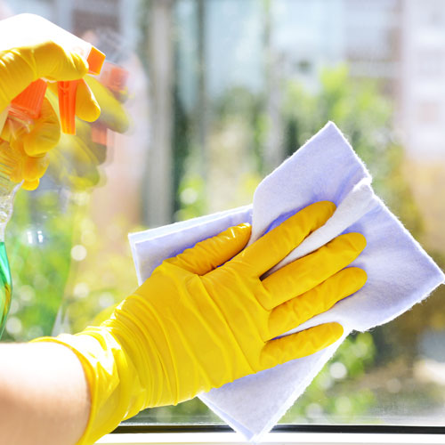 Gloved hands cleaninng window